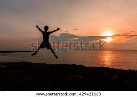 Happy man Jumping in Sea beach Sunset silhouette.Holiday vacation concept Copy space
