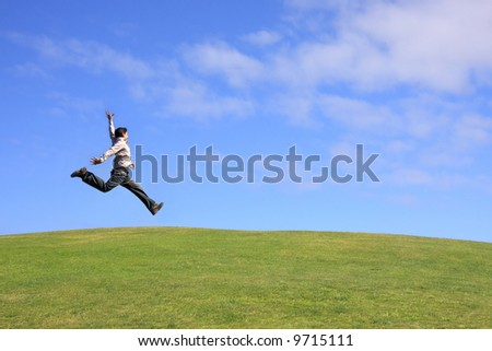 Happy man jumping on a beautiful landscape - stock photo