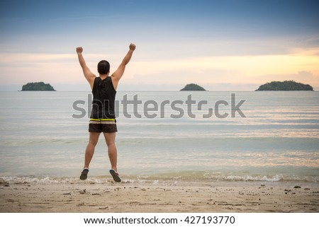 Happy man jumping on the beach at the day time