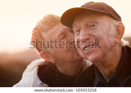 Happy man kissed by wife outside during sunset - stock photo