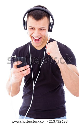 happy man listening favorite playlist on mobile phone wearing headphones - stock photo