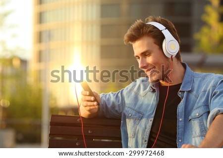 Happy man listening to music from a smart phone with a warmth sunset city background - stock photo