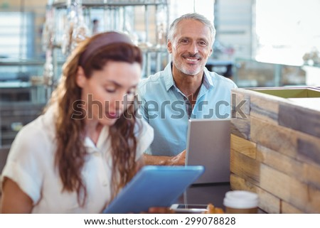 Happy man looking at camera and using laptop in the bakery store
