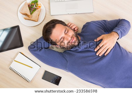 Happy man lying on floor surrounded by his things at home in the living room - stock photo