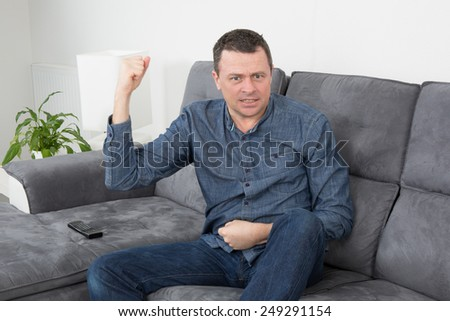Happy Man lying on sofa with his fist  in the air - stock photo