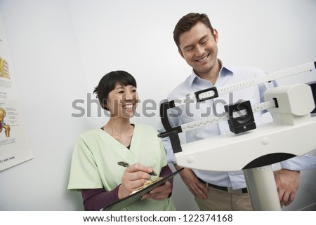Happy man measuring weight with doctor making notes - stock photo