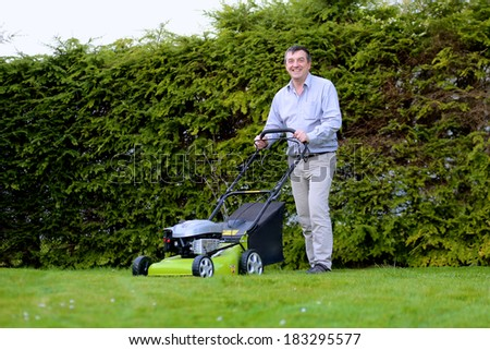 Happy man mowing the lawn in the backyard of his house at the free time on a sunny summer day