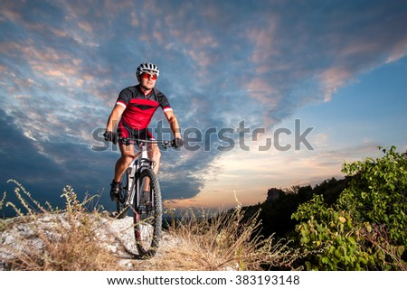 Happy man on a mountain bike races downhill in the nature against blue cloudy evening sky. Cyclist is wearing red sportswear helmet gloves and red glasses. Cross country biking. - stock photo