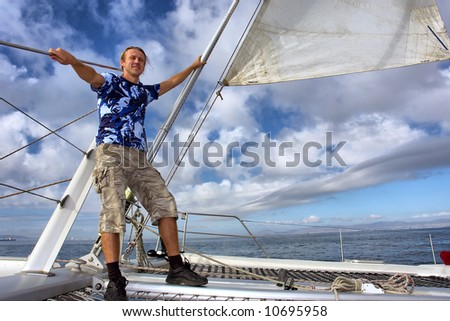 Happy man on sailboat desk against thunderstorm sky. Shot near Waterfront, Cape Town, Western Cape, South Africa.