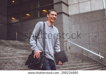 Happy man on stairs in casual clothes and laptop.
