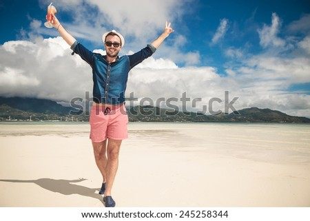 Happy man on the beach looking at the camera while holding both hands in the air. He is holding a cocktail in his right hand. - stock photo