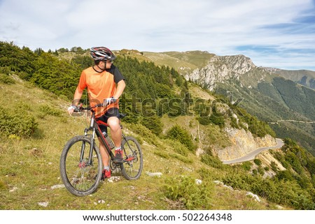 Happy man on the mountain trains in dangerous terrain cycling. Extreme mountain ride