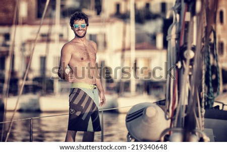Happy man on the sailboat, enjoying beautiful sunset in the sea, cruise on luxury water transport, great summer adventure concept - stock photo