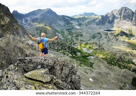 Happy man on the top of the hill with open arms looking at wonderful scenery during summer touristic trip