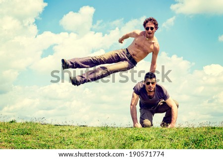 Happy man overcomes another man with fluffy clouds in background  - stock photo
