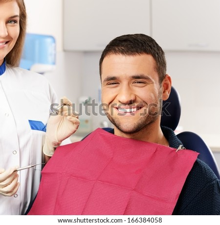 Happy man patient and smiling woman dentist at dental surgery - stock photo