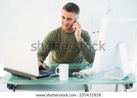 Happy man phoning and using laptop in his office - stock photo