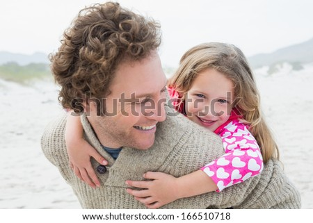 Happy man piggybacking his cheerful daughter at the beach - stock photo