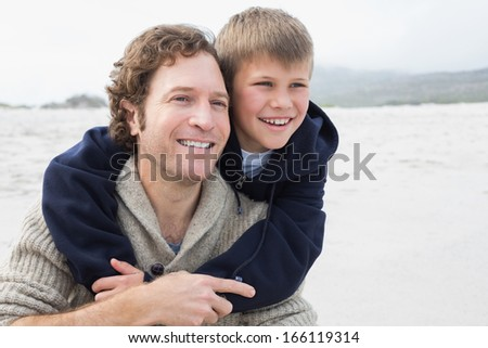 Happy man piggybacking his cheerful son at the beach - stock photo