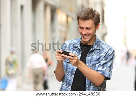 Happy man playing game with a smart phone in the street - stock photo