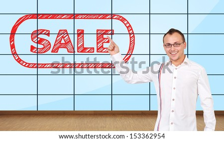 happy man pointing at plasma wall with sale symbol - stock photo