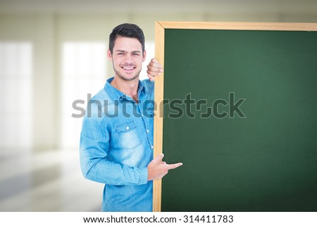 Happy man pointing to card against bright room with windows