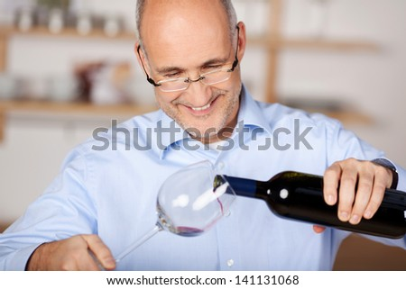 Happy man pouring wine into a glass at home - stock photo