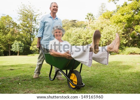 Happy man pushing his laughing wife in a wheelbarrow outside in sunshine - stock photo