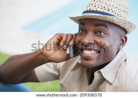 Happy man relaxing in his garden talking on phone on a sunny day - stock photo