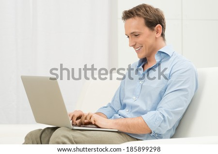 Happy Man Relaxing On Sofa Using Computer