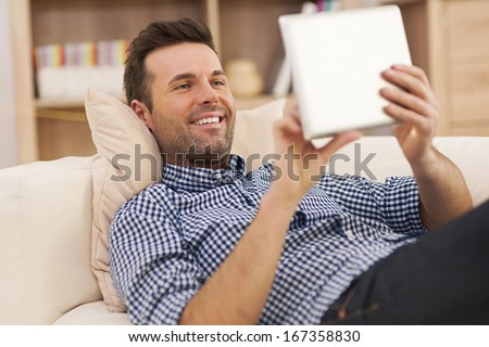 Happy man relaxing on sofa with digital tablet  - stock photo