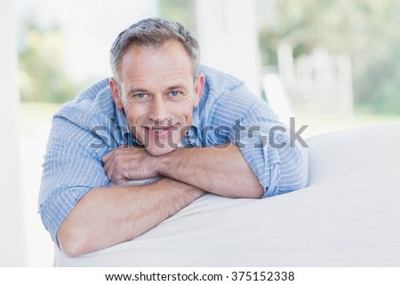 Happy man relaxing on the couch in the living room - stock photo