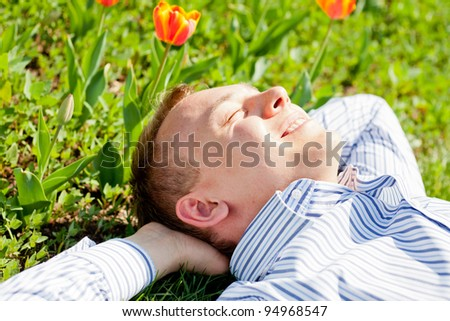 Happy man relaxing outdoors lying on grass - stock photo