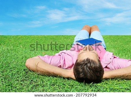 Happy man relaxing outdoors lying on the grass - stock photo