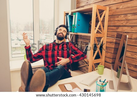 Happy man relaxing while listening music and gesturing like playing on guitar - stock photo