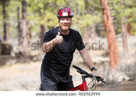 Happy man riding a mountain bike in the woods - stock photo