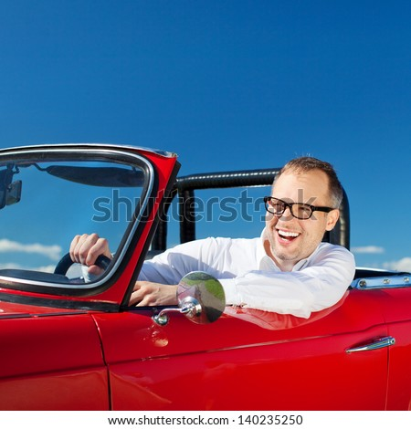 Happy man riding a red convertible car over the bright blue sky - stock photo