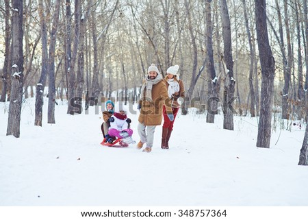 Happy man riding kids on sledge while spending time in winter park - stock photo