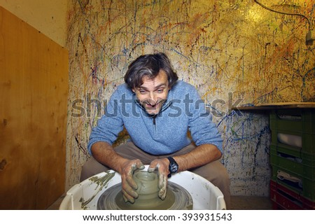 happy man shaping clay pottery bowl