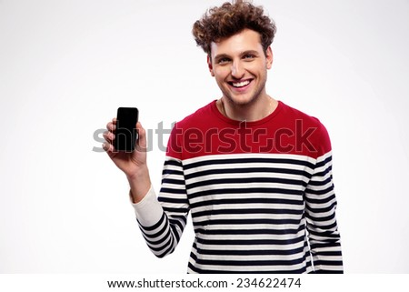 Happy man showing a blank smartphone display - stock photo