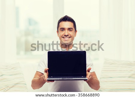 happy man showing laptop blank screen at home