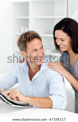 Happy man showing something on the newspaper to his girlfriend in the kitchen