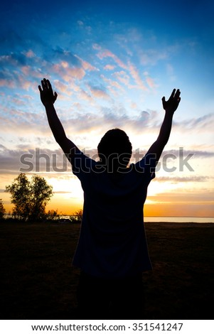Happy Man Silhouette with Hands Up on the Sunset Background