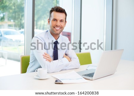 Happy man sitting at desk in the office - stock photo
