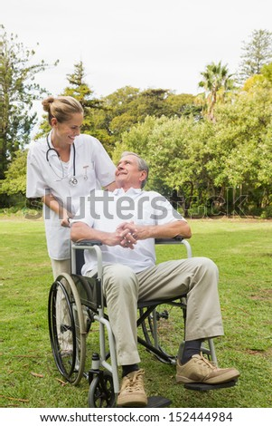 Happy man sitting in a wheelchair talking with his nurse pushing him at the park on sunny day