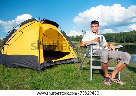 happy man sitting in armchair near yellow tent