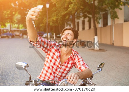 Happy man sitting on his scooter and making a selfie photo on a bright sunny summer day - stock photo