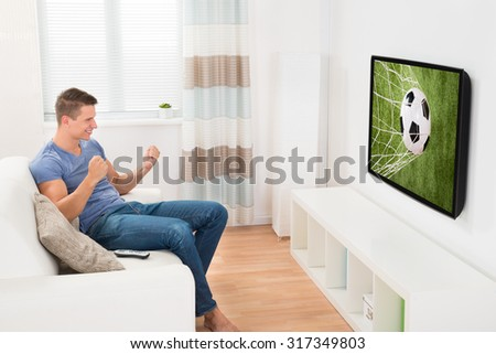 Happy Man Sitting On Sofa Watching Sport On Television