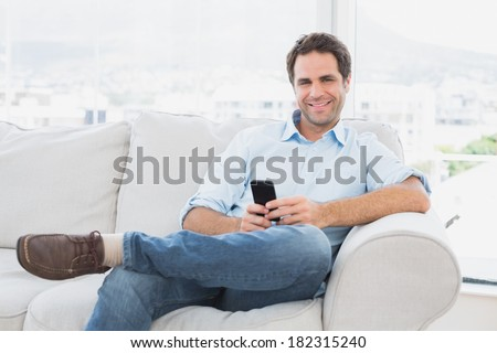 Happy man sitting on the couch using his smartphone at home in the living room - stock photo