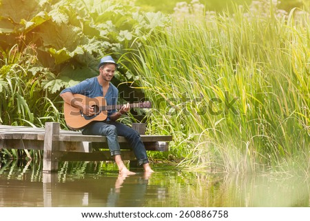 happy man sitting on the edge of a pontoon, feet in the water and playing guitar, he wears a blue hat - stock photo